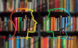 Silhouetten von zwei Köpfen vor einem Bücherregal