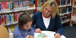 Eine Frau liest mit einem Mädchen ein Buch