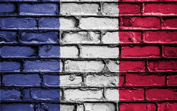 Eine Backsteinmauer in den Farben der französischen Flagge (Blau, Weiß und Rot)