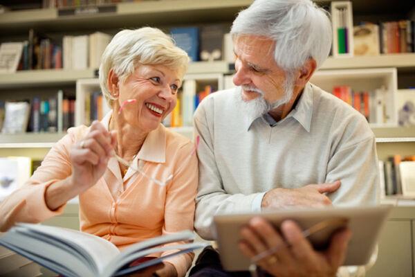 Paar mit Buch und Tablet-PC