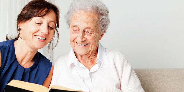 Junge Frau liest älterer Dame vor
