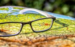 Eine Brille liegt mitten auf einer Landkarte