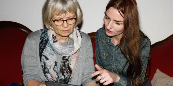 Eine junge Frau erklärt einer älteren Frau den Umgang mit einem Tablet-PC