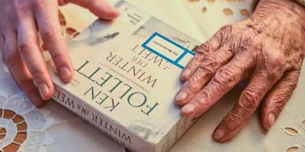 Eine junge Hand und eine ältere Hand halten ein Hörbuch