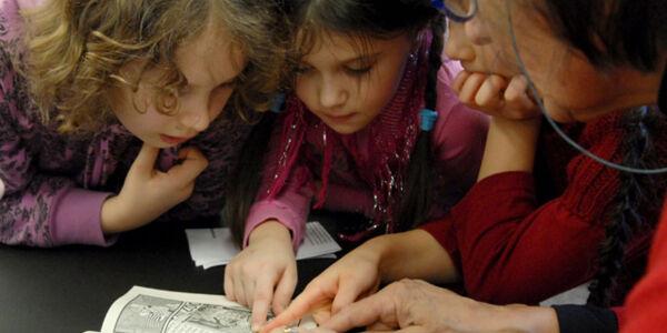 Eine Vorleserin liest Kindern ein Buch vor