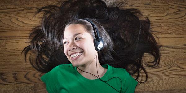 Junge lachende Frau mit Kopfhörern