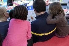 Kinder sehen sich gemeinsam mit einem Erwachsenen ein Buch an