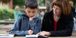 Eine Frau liest mit einem Jungen ein Buch