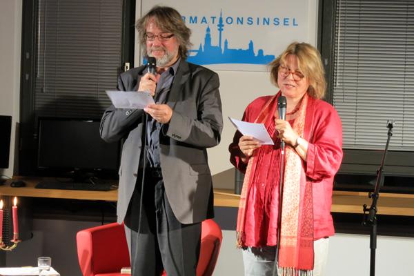 Ein Mann und eine Frau stehend mit Mikrofonen in den Händen