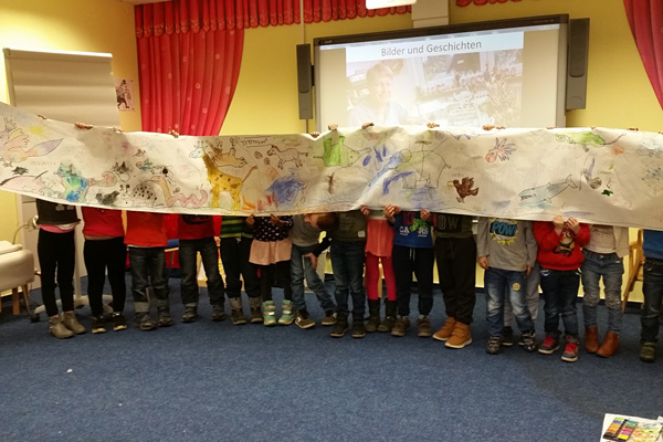 Kinder präsentieren ein Plakat