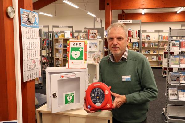 Ein Mann präsentiert einen Defibrillator