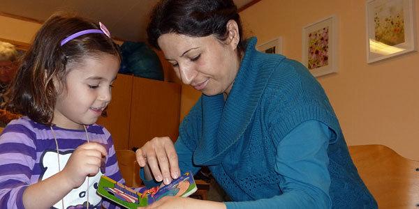Eine Frau zeigt einem Kind ein Bilderbuch