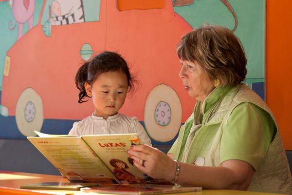 Eine Frau liest einem Mädchen vor