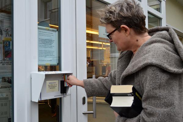 Kundin öffnet Bücherhalleneingang mit ihrer Kundenkarte
