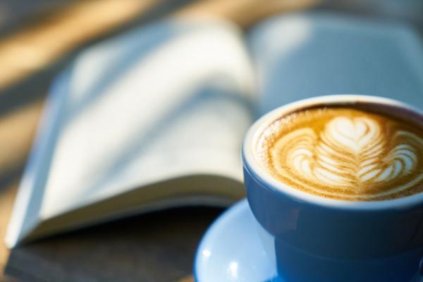 Ein aufgeschlagenes Buch, davor eine Tasse Cappucino