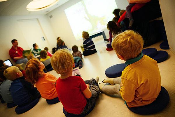 Kinder sitzen im Kreis und hören einer Geschichte zu