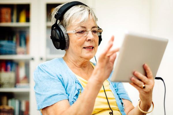 Seniorin mit Kopfhörern und Tablet-PC