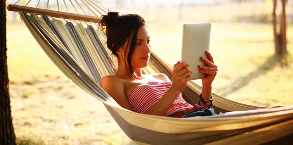 Frau in einer Hängematte liest ein eBook